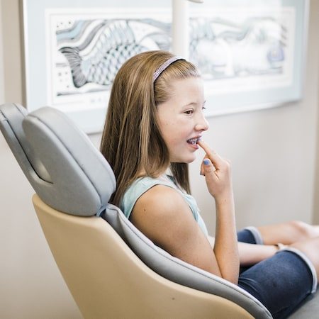 Young girl pointed to her braces on her teeth as she learns about braces care.