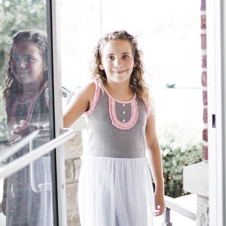 Little girl in a grey dress walking into our Nashville Orthodontic office for her orthodontic treatment.