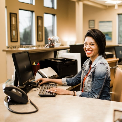 An orthodontic front desk coordinator at Lucas Orthodontic Care smiling at her desk ready to help you get the most from your orthodontic insurance.